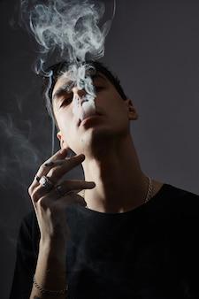 Retrato de um jovem moda cara de fumo em contraste preto e branco.