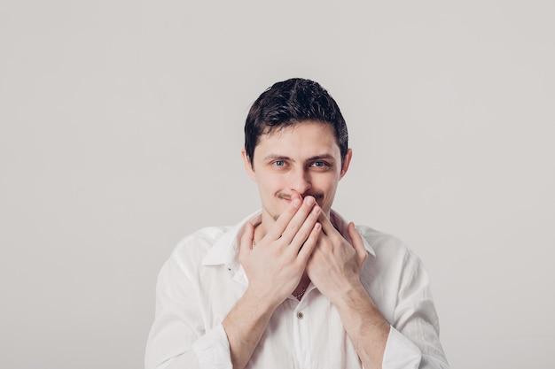 Retrato de um jovem moreno em camisa branca cobre a boca com as mãos no fundo cinza. cara sabe o segredo, mas não vai contar. luz suave