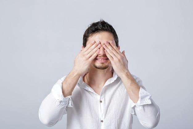 Retrato de um jovem moreno em camisa branca fecha os olhos com as mãos no fundo cinza. eu não quero ver isso.