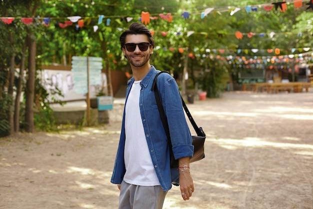 Retrato de um jovem muito alegre com barba, caminhando ao longo do jardim da cidade, sorrindo e com uma aparência positiva, usando roupas casuais e óculos escuros