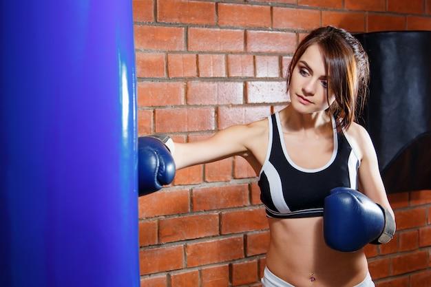 Retrato, de, um, jovem, mulher bonita, com, luvas boxing, em, treinamento, em, ginásio