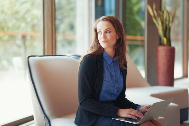 Retrato, de, um, jovem, mulher negócio, usando computador portátil, em, escritório