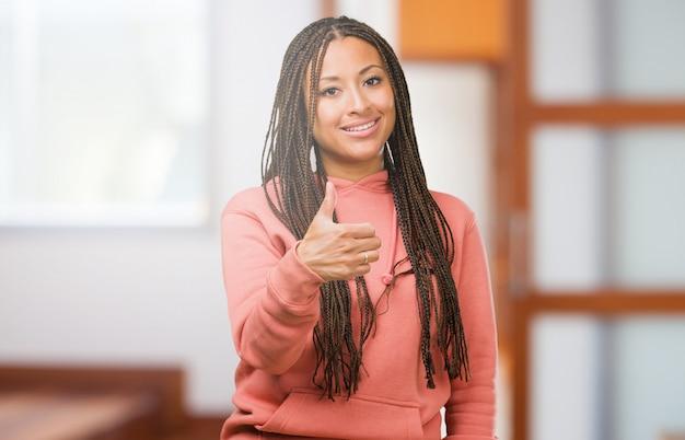 Retrato, de, um, jovem, mulher preta, desgastar, tranças, alegre, e, excitado, sorrindo, e, levantando, dela, polegar cima