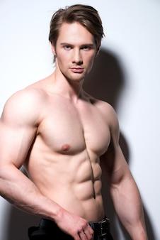 Retrato de um jovem musculoso sexy, posando em uma parede branca com sombras de contraste.