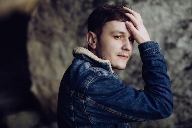 Retrato de um jovem nas montanhas. um homem segura a mão atrás da cabeça