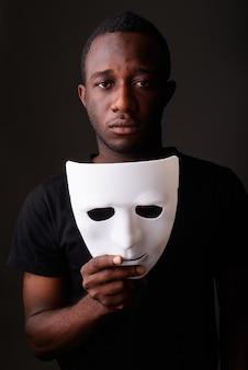 Retrato de um jovem negro africano em um quarto escuro segurando uma máscara