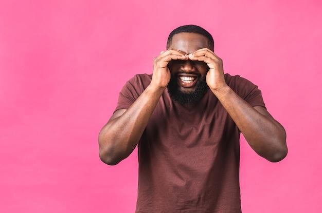 Retrato de um jovem negro afro-americano alegre isolado sobre um fundo rosa.