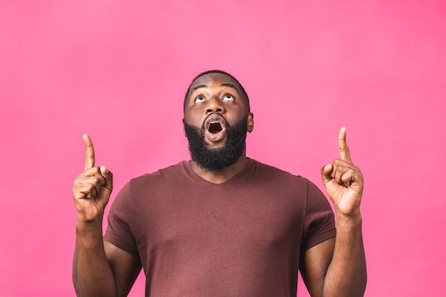 Retrato de um jovem negro afro-americano feliz com um sorriso casual, apontando para cima com o dedo, olhando na câmera com a expressão do rosto animado isolada sobre o fundo rosa.