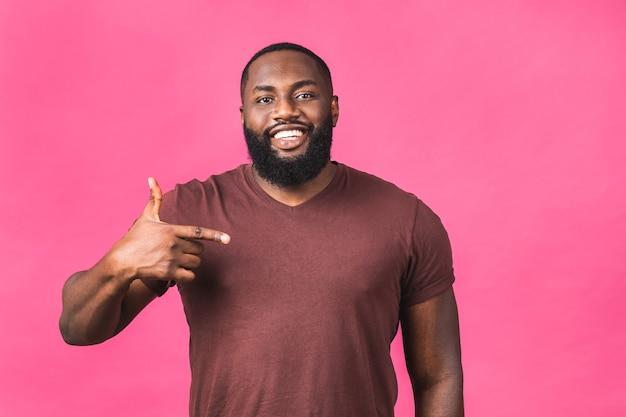 Retrato de um jovem negro afro-americano feliz com um sorriso casual, apontando para o lado com o dedo, olhando na câmera com expressão de rosto animado isolada sobre fundo rosa.