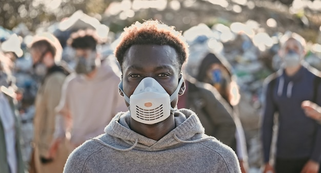 Retrato de um jovem negro e triste com uma máscara de gás em meio a uma fumaça tóxica