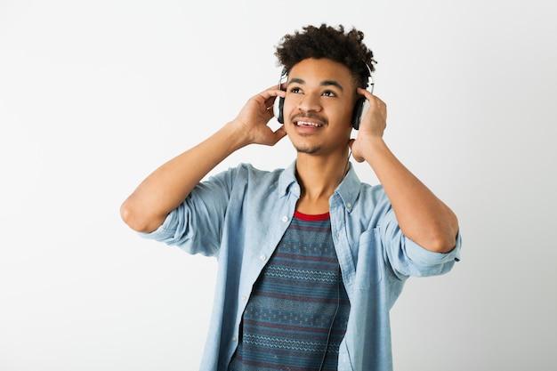 Retrato de um jovem negro hippie posando no fundo da parede do estúdio branco isolado, roupa elegante, penteado afro engraçado, ouvindo música em fones de ouvido, sorrindo, feliz, curtindo, olhando para cima