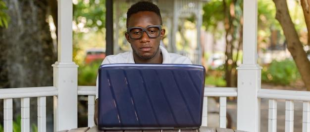 Retrato de um jovem nerd africano como um estudante com óculos no parque ao ar livre