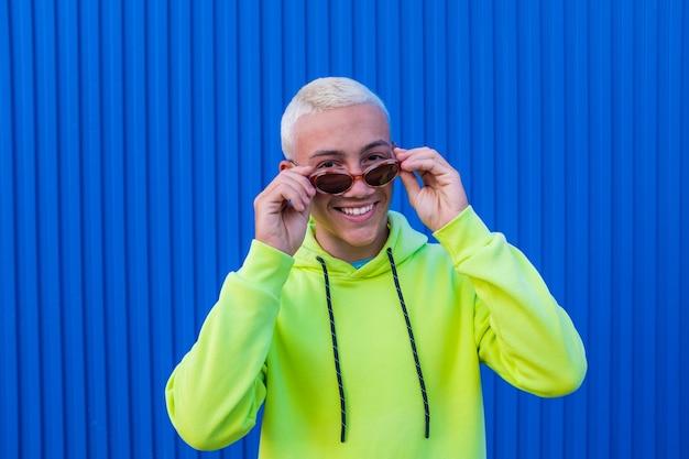 Retrato de um jovem ou adolescente sorrindo e se divertindo usando óculos de sol da moda e um suéter verde-limão com fundo azul colorido - pessoas alegres do milênio curtindo