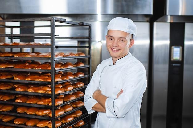 Retrato de um jovem padeiro com forno industrial com bolos em uma padaria