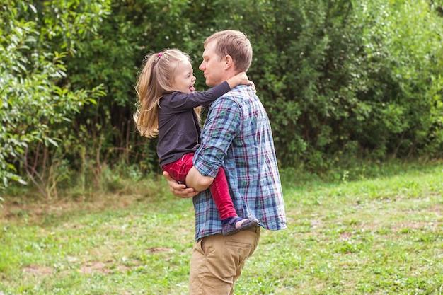 Retrato de um jovem pai e filha de 2 a 3 anos olhando para a câmera e brincando no gramado de verão no parque