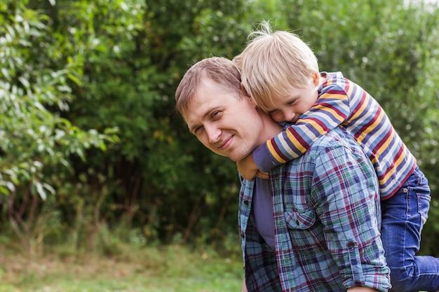 Retrato de um jovem pai e filho olhando para a câmera e brincando no gramado de verão no parque