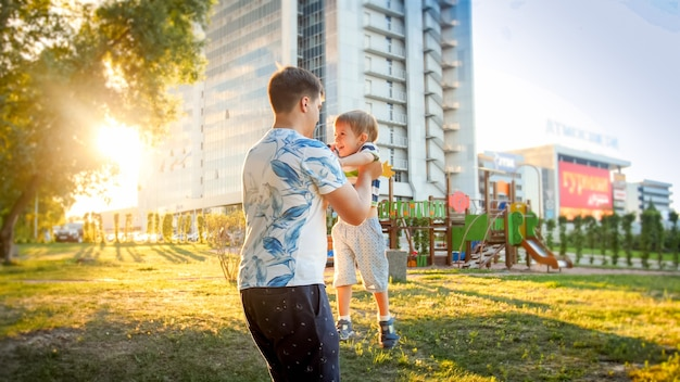 Retrato de um jovem pai feliz abraçando e girando seu filho pequeno sorridente no parque