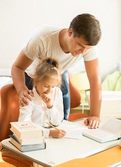 Retrato de um jovem pai olhando para a filha fazendo o dever de casa