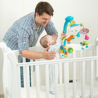 Retrato de um jovem pai segurando seu filho bebê de 9 meses no berço