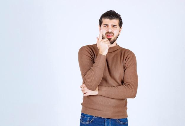 Retrato de um jovem pensando e em pé contra uma parede branca.