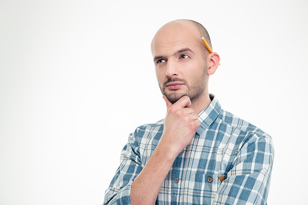 Retrato de um jovem pensativo concentrado em uma camisa quadriculada com lápis atrás da orelha, isolado sobre uma parede branca