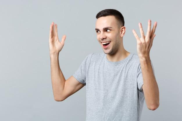 Retrato de um jovem perplexo e animado em roupas casuais, olhando para o lado, levantando-se estendendo as mãos