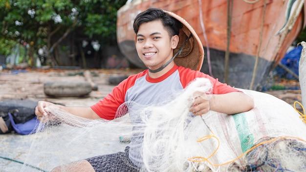Retrato de um jovem pescador preparando uma rede de pesca na praia