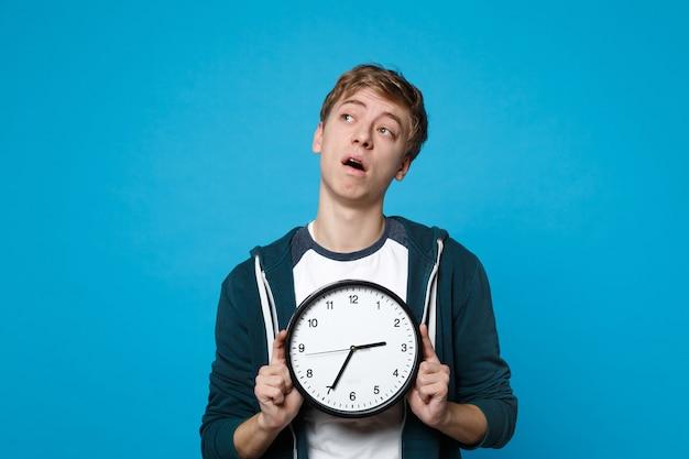 Retrato de um jovem preocupado com roupas casuais, segurando o relógio redondo isolado na parede azul. o tempo está se esgotando. emoções sinceras de pessoas, conceito de estilo de vida.