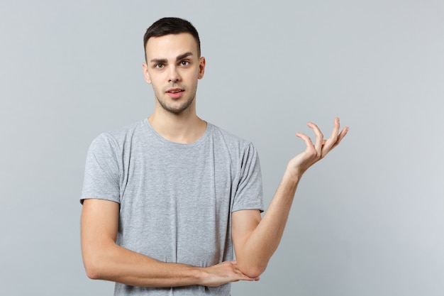 Retrato de um jovem preocupado perplexo em roupas casuais, estendendo as mãos