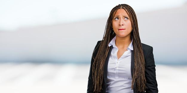 Retrato, de, um, jovem, pretas, mulher negócio duvidando, e, confundido