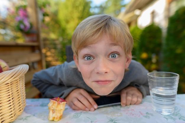 Retrato de um jovem rapaz bonito com cabelo loiro no jardim do quintal em casa