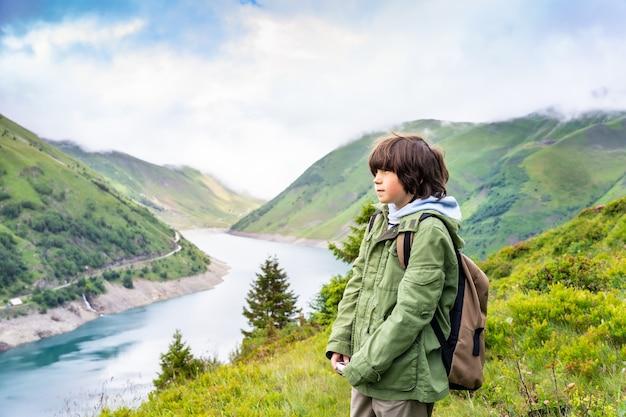 Retrato de um jovem rapaz com uma mochila com uma jaqueta verde de pé nas montanhas perto de um belo lago nos alpes franceses, olhando para longe com uma cara séria. caminhadas com crianças.