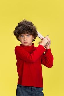 Retrato de um jovem rapaz encaracolado com roupa vermelha em fundo amarelo studio. infância, expressão, educação, conceito divertido.