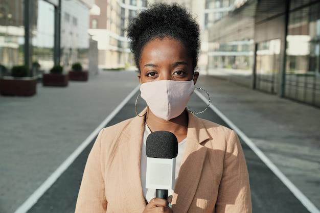 Retrato de um jovem repórter africano na máscara protetora segurando um microfone e olhando para a câmera em pé na cidade