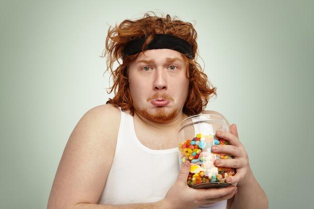 Retrato de um jovem ruivo com excesso de peso engraçado com uma faixa esportiva na cabeça e um olhar triste e infeliz
