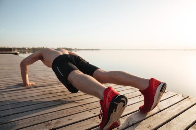 Retrato de um jovem saudável, fazendo flexões