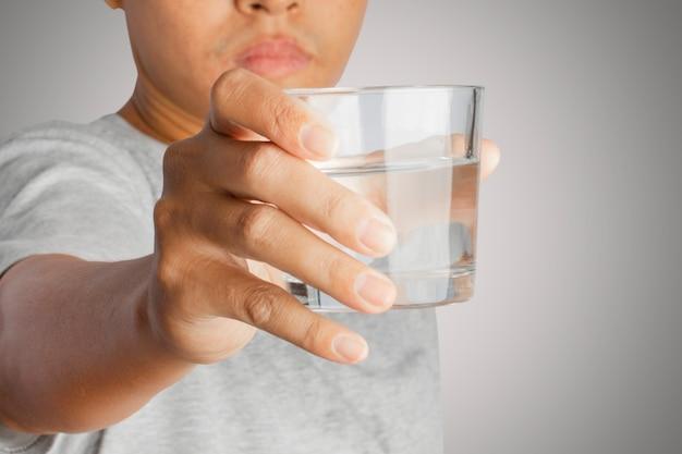 Retrato de um jovem segurando o copo de água potável na mão.