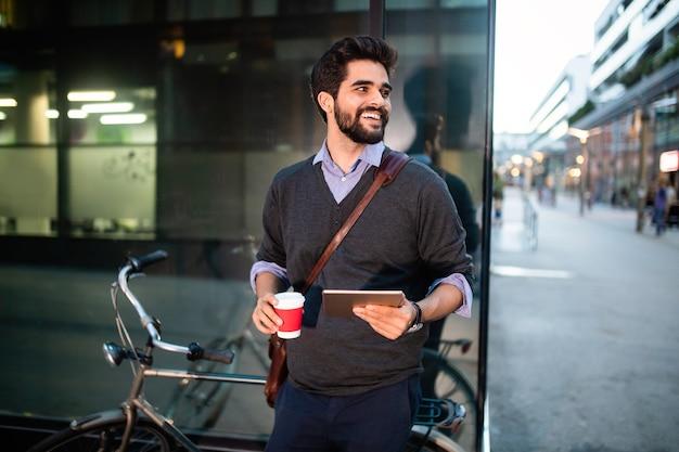 Retrato de um jovem segurando um tablet e um café ao ar livre