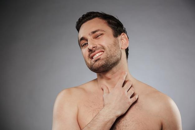 Retrato de um jovem sem camisa, examinando a pele