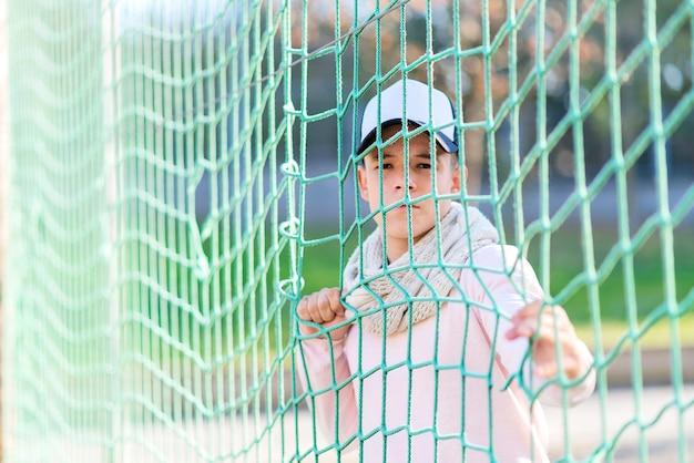Retrato de um jovem sério, encostado em uma cerca de rede enquanto olha para a câmera