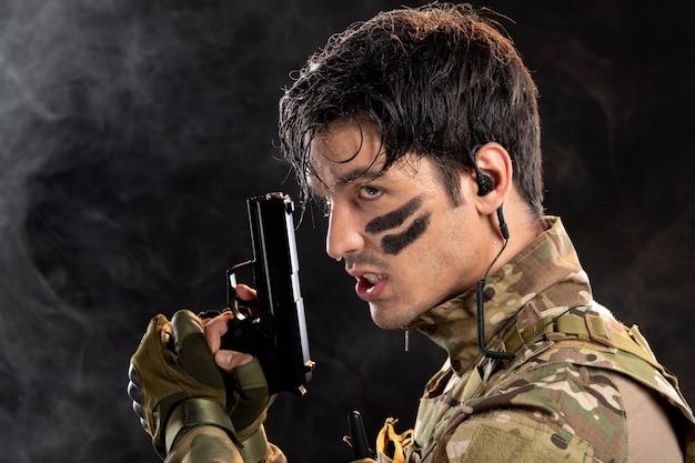 Retrato de um jovem soldado camuflado segurando uma arma na parede preta