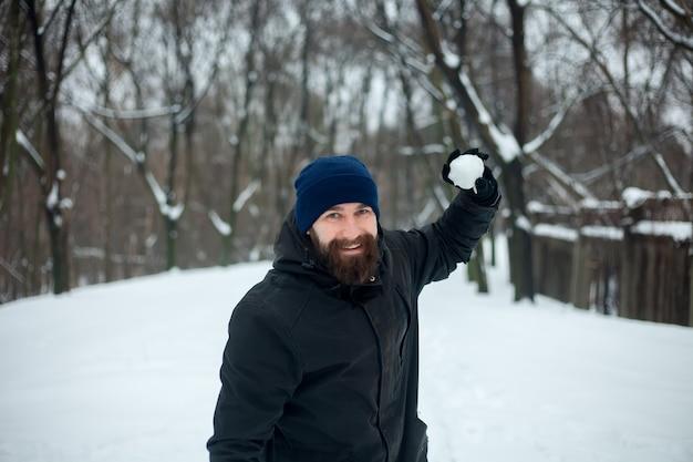 Retrato de um jovem sorridente com um chapéu e uma bola de neve na mão