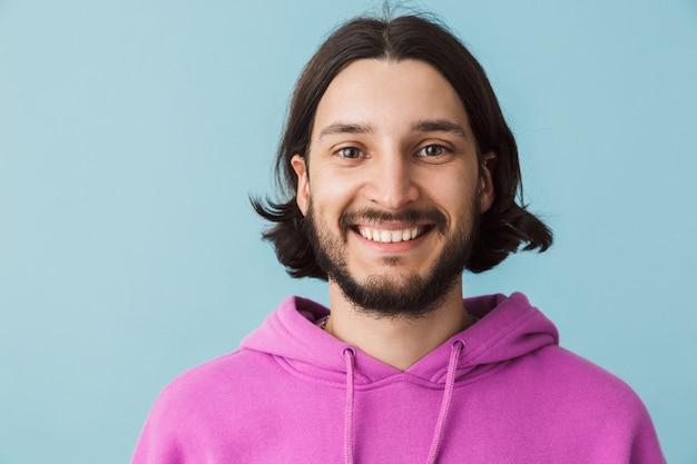 Retrato de um jovem sorridente e barbudo moreno com capuz isolado na parede azul