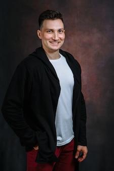 Retrato de um jovem sorridente em uma jaqueta preta, camiseta branca e calça jeans vermelha