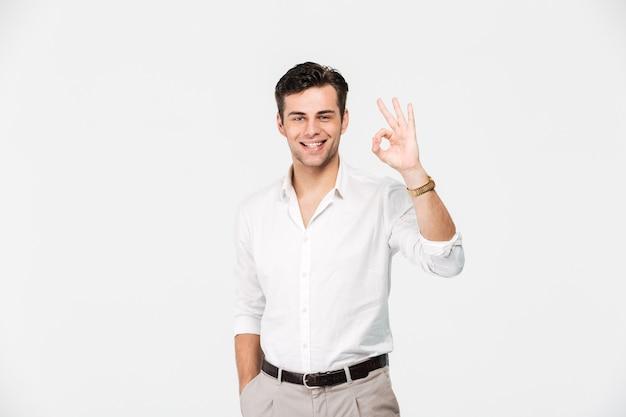 Retrato de um jovem sorridente na camisa mostrando ok