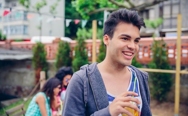 Retrato de um jovem sorridente segurando um coquetel de água com infusão ao ar livre com seus amigos sentados em um dia de verão