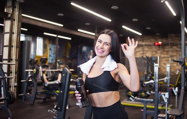 Retrato de um jovem sorridente sportswomanin alegre em roupas esportivas e toalha em volta do pescoço, garrafa de água na mão mostra dedos ok sinal no ginásio