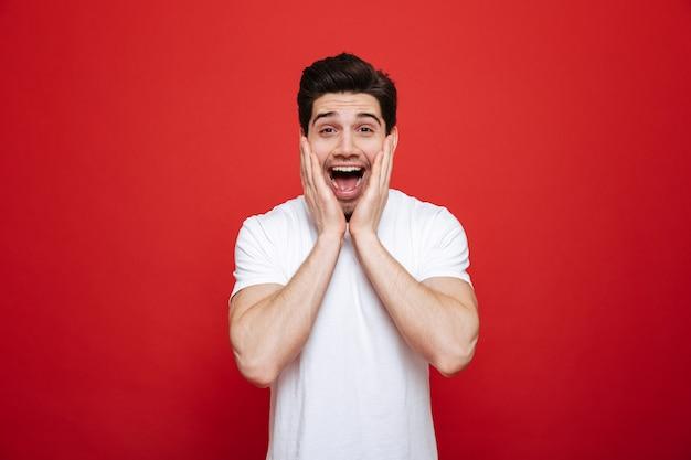 Retrato de um jovem surpreso em camiseta branca