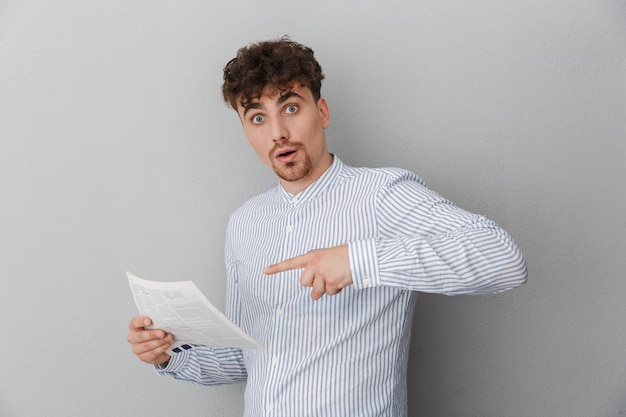 Retrato de um jovem surpreso, vestido com uma camisa, pensando enquanto segura e lê um jornal ou revista, isolado sobre a parede cinza