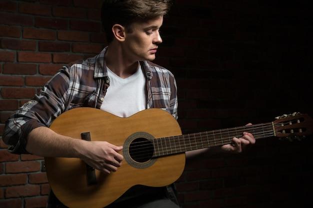 Retrato de um jovem tocando violão com uma parede de tijolos na parede